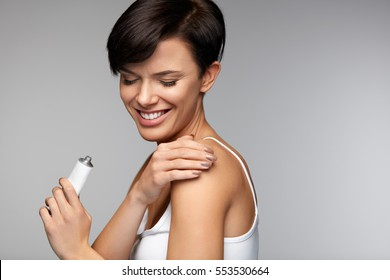 Injury Treatment. Beautiful Woman Feeling Pain In Shoulders, Applying Medical Muscle Cream On Arm, Holding Cream Tube In Hand. Female Putting Lotion On Painful Shoulder. Health Care. High Resolution