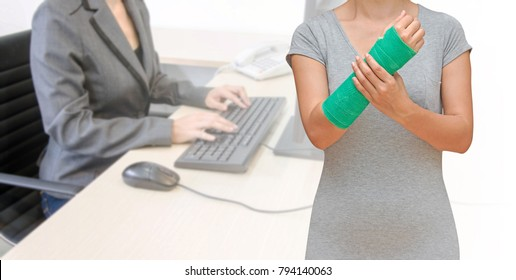 Injury woman with green cast on hand and arm on blurred background employees with computer in office, body injury concept.