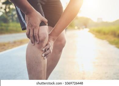 Verletzung durch das Konzept des Workout: Der Asiane benutzt Hände am Knie, während er im Park auf der Straße läuft. Morgenbespielen, Sonnenlicht und warmer Effekt mit Kopienraum für Text oder Design