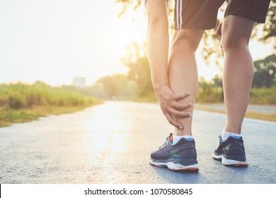 Verletzung durch das Konzept des Workout: Der asiatische Mann hält sich am Knöchel fest, während er im Park auf der Straße läuft. Fokus auf den Knöchel.