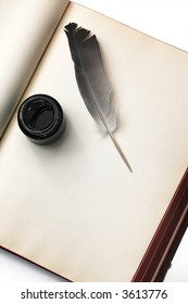 ink bottle and a quill on an old notebook