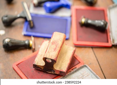 Ink box and rubber stamp on wooden table