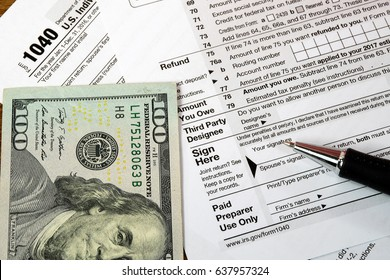 ink pen and hundred dollar bill on 1040 income tax form