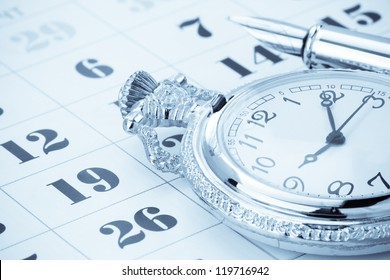 ink pen and watch on calendar background