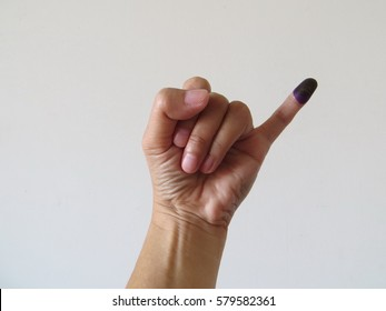 Inked pinky finger of a woman's hand. Purple ink blots from voter's finger provides evidence of the governor election (pilkada) in Jakarta, Indonesia.