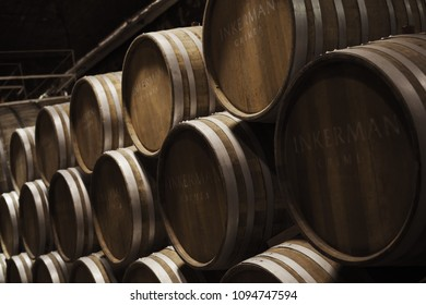 Inkerman, Crimea - May 7, 2018: Wooden barrels in dark wine factory hall, close-up photo with selective focus