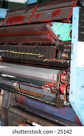 An ink-splattered newspaper web-offset printing press unit.