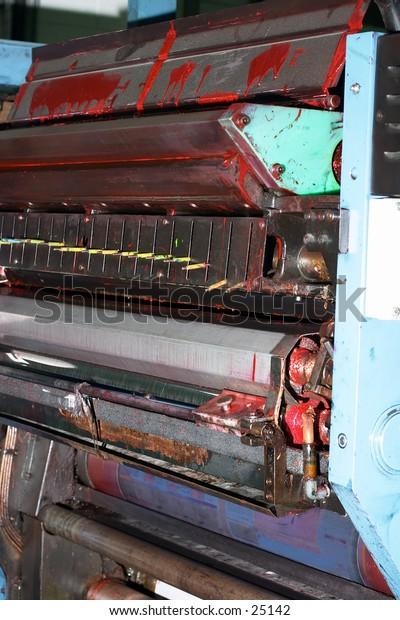 An ink-splattered newspaper web-offset printing press unit.