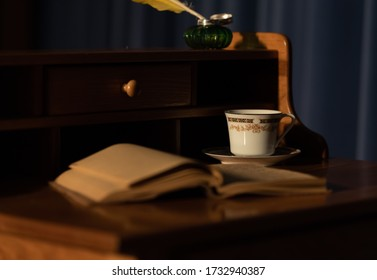 Inkwell, feather pen, open book and teacup on antique desk. A taste of time gone by. Perhaps an author penning her latest or a victorian gentlewoman writing in her diary.