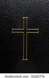Inlaid golden cross on the cover of a black bible