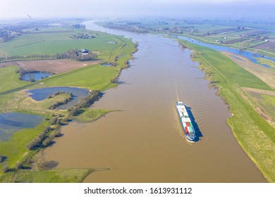 Inland container barge on River Lek aerial view near the village of Ravenswaaij, Gelderland, Netherlands