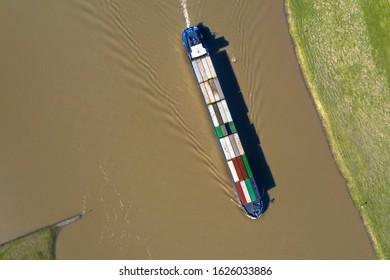 Inland container vessel on River Lek aerial view near the village of Ravenswaaij, Gelderland, Netherlands