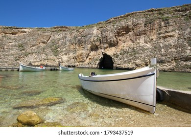 Inland sea tunnel Diversite near former Azure window site on Dwejra at Gozo island in Malta. Empty boats sit in inland sea in front of rock formation separating them from the sea.