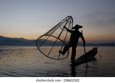 INLE LAKE, BURMA, December 14, 2014 : Fishermen on Inle lake in morning light. These fishermen are practicing a distinctive rowing style, wrapping a leg around the oar.