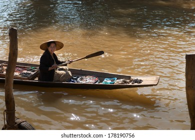 INLE LAKE, MYANMAR - 07 JAN 2014: Floating vendor on small  long wooden boat with trinkets and bijouterie row at turbid water
