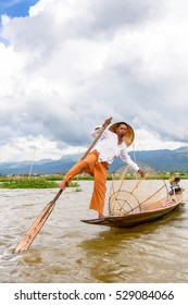 INLE LAKE, MYANMAR - AUG 30, 2016: Unidentified Burmese fisherman on a boat with a special handmade net. This is the traditional way of fishing in Myanmar