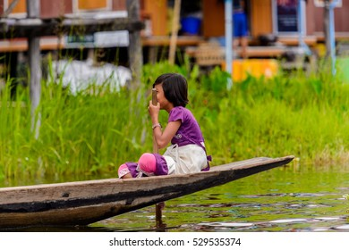 INLE LAKE, MYANMAR - AUG 30, 2016: Unidentified Burmese girl in bamboo boat sails over the Inle Sap,a freshwater lake located in the Nyaungshwe Township of Taunggyi District of Shan State, Myanmar