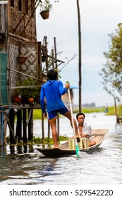 INLE LAKE, MYANMAR - AUG 30, 2016: Unidentified Burmese people in bamboo boat sails over the Inle Sap,  a freshwater lake located in the Nyaungshwe Township of Taunggyi District of Shan State, Myanmar
