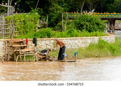 INLE LAKE, MYANMAR - AUG 30, 2016: Unidentified Burmese people clean clothes in the lake. 68 per cent of Myanma people belong to Bamar ethnic group