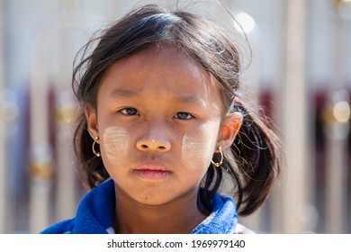 Inle Lake, Myanmar, Burma - Jan 12, 2016 : young girl from Myanmar with Tanaka on her face in yard near local school, Burma. Tanaka is a yellowish-white cosmetic paste made from crushed bark