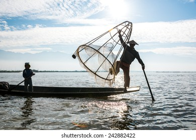 INLE LAKE, MYANMAR - CIRCA DECEMBER 2014 : Fisherman shows how to catch a fish with traditional method with handmade net on the boat in Inle lake, Myanmar.