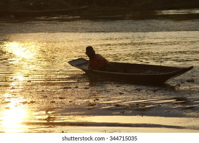 INLE LAKE, MYANMAR - CIRCA FEBRUARY 2007: Man in wooden fishing boat at sunset, boat in silhouette