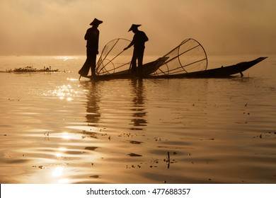 INLE LAKE, MYANMAR, December 14, 2014 : Fishermen on Inle lake in morning fog. These fishermen are practicing a distinctive rowing style, wrapping a leg around the oar.
