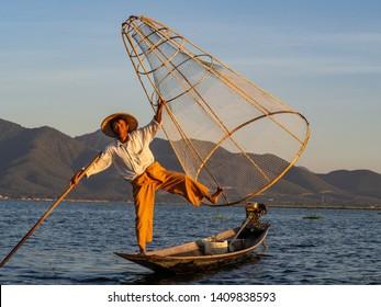 Inle Lake, Myanmar - December 2018: traditional fisherman poses for photos on Inle Lake