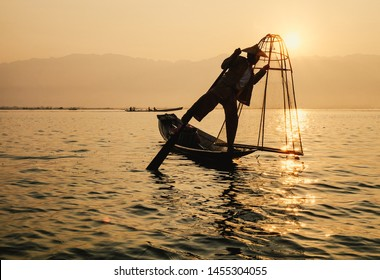 Inle Lake, Myanmar - Feb 16, 2016. Intha man using the unique methods of rowing and catching fish on Inle Lake (Shan State).