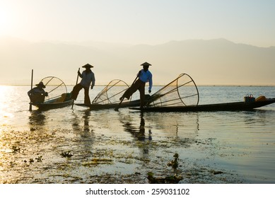 INLE LAKE, MYANMAR - FEB 26: Three fishermen catches fish for food on February 26, 2015 on Inle Lake, Myanmar. Intha people possess the feet-rowing style and the unique fishing equipment.