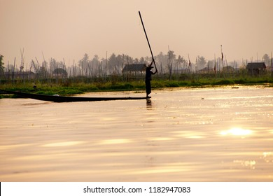 INLE LAKE, MYANMAR - FEB 28, 2015 - Fisherman slaps water with long pole to chase fish into his net,  Inle Lake,  Myanmar (Burma)