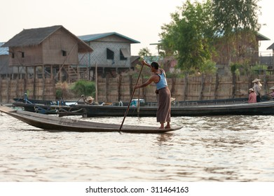 INLE LAKE, MYANMAR - FEBRUARY 15: Unidentified man rowing a wooden boat in Inle Lake with its leg-rowing and fishing. Intha people is a major tourist destination on Feb 15, 2011 in Inle lake, Myanmar.