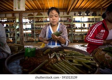 INLE LAKE, MYANMAR - JAN 28, 2014: Burmese woman works making cheroot cigars in shop on Inle Lake