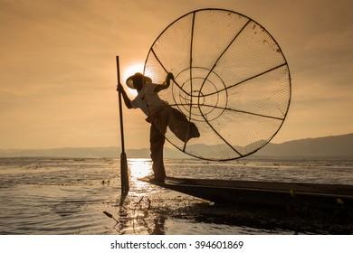 INLE LAKE, MYANMAR - JANUARY 14, 2016: Unidentified Burmese fisherman on bamboo boat catching fish in traditional way with handmade net. Inle lake, Myanmar, Burma
