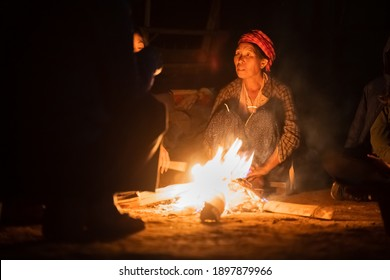INLE LAKE, MYANMAR - JANUARY 16, 2020: A local elderly woman sits by a bright campfire with tourists sat beside her at Inle Lake, Myanmar.