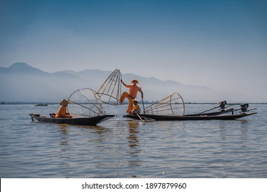 INLE LAKE, MYANMAR - JANUARY 18, 2020: Three fishermen in traditional clothing sat in their wooden boats with mountains in the background at Inle Lake, Myanmar.