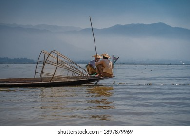 INLE LAKE, MYANMAR - JANUARY 18, 2020: Two fishermen in traditional clothing sat in their wooden boats with mountains in the background at Inle Lake, Myanmar.