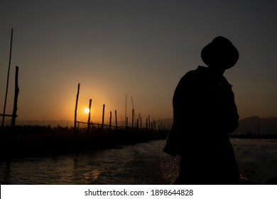 INLE LAKE, MYANMAR - JANUARY 18, 2020: Silhouette of a local man steering a boat at sunset on Inle Lake.