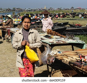 INLE LAKE, MYANMAR - JANUARY 25, 2014:  Undefined burmese woman on a local floating market with boats and local sellers.
