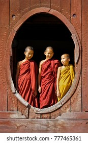 INLE LAKE, MYANMAR, JANUARY 28, 2011. Novice Buddhist monks stand in the oval window of Shwe Yan Pye monastery near Nyaungshwe.