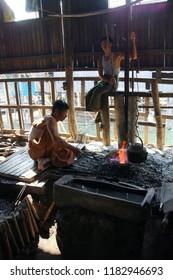 INLE LAKE, MYANMAR - MAR 1, 2015 - Blacksmith heating iron in a charcoal fire,  Inle Lake,  Myanmar (Burma)