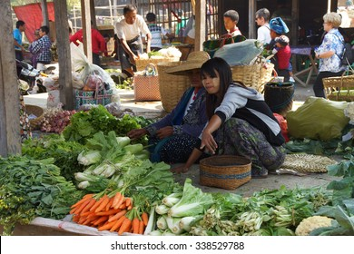 INLE LAKE, MYANMAR - MAR 1, 2015 - Young woman selling fresh vegetables at the weekly market on  Inle Lake,  Myanmar (Burma)
