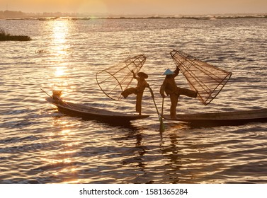 Inle lake, Myanmar - Nov 10, 2019 : local Inle Lake fishermen standing with balancing.Their hands, on the other hand, hold a conical net that they use for catching the fish on sunrise,sunset time.