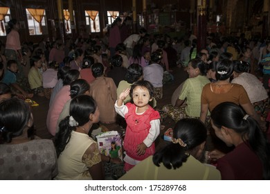 INLE LAKE, MYANMAR - NOVEMBER 3;Small Asian child standing amongst crowd attending a novitiation ceremony sitting on hall floor waves out on November 3, 2013 at Inle Lake, Myanmar.