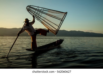 Inle Lake, Shan State, Myanmar - Nov 6, 2013: Burmese man with fishing tool rowing a small boat in Inle Lake. The Inle natives are famous for their unique leg rowing technique.