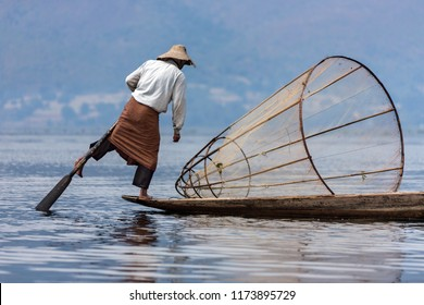 Inle. Myanmar. 02.03.13. Leg rowing fisherman on Inle Lake, Shan State, Myanmar. This unique style of rowing evolved because it's difficult to see the fish while sitting. Standing gives a better view.