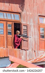 INLE, MYANMAR - NOVEMBER 28, 2016: Buddhist novice boy with a BB gun in a monastery at Inle lake, Myanmar