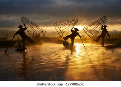 INLE, MYANMAR - NOVEMBER 28: Three fishermen perform the traditional fishing method on 28/11/2018 in Myanmar. Fishing with special shaped fishnets and one legged rowing is distinctive for Myanman