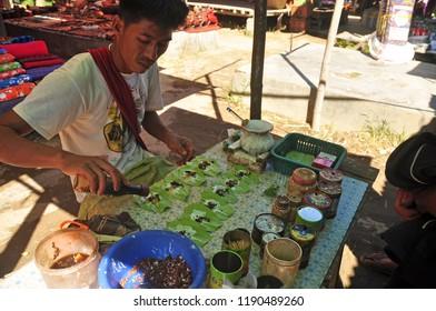 INLE, MYANMAR - NOVEMBER 29, 2015: Man preparing green kratom on market, Ethnic man sitting at able and preparing kratom natural drugs on lake local market. Asian narcotic