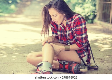 in-line skating injured young woman suffering from pain sitting on the ground touching painful knee waiting in need for medical help outdoors on summer day